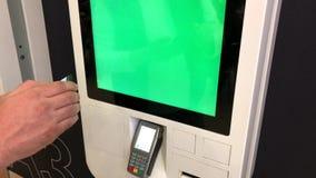 Homme commandant les aliments de préparation rapide dans le kiosque d'écran tactile de libre service banque de vidéos