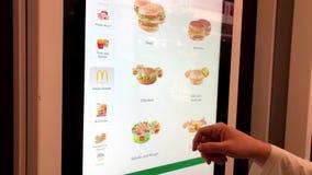 Homme commandant les aliments de pr?paration rapide dans le kiosque d'?cran tactile de libre service banque de vidéos