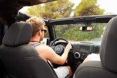 Homme conduisant la voiture à couvercle serti le long de la route de campagne Photos libres de droits