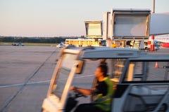 Homme conduisant le chargeur dans l'aéroport Photos libres de droits