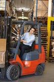 Homme conduisant le chariot gerbeur dans l'entrepôt images libres de droits