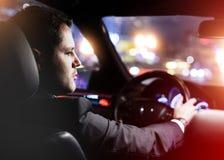 Homme conduisant une voiture la nuit images stock