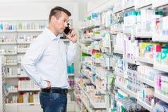 Homme confus à l'aide du téléphone portable dans la pharmacie photographie stock libre de droits