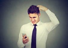 Homme confus naïf d'affaires ayant des ennuis avec son smartphone photos stock