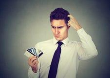 Homme confus regardant beaucoup de cartes de crédit incertaines lesquels pour choisir photo stock