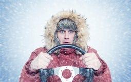 Homme congelé dans des vêtements rouges d'hiver avec un volant, tempête de neige de neige Conducteur de voiture de concept images libres de droits