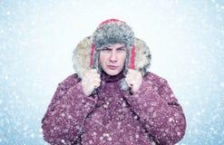 Homme congelé dans des vêtements rouges d'hiver, froid, neige, tempête de neige photographie stock