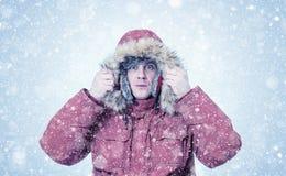 Homme congelé dans des vêtements rouges d'hiver, froid, neige, tempête de neige photos stock