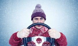 Homme congelé dans le chandail et le chapeau avec un volant, tempête de neige de neige Conducteur de voiture de concept image stock