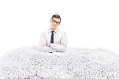 Homme contrarié se tenant dans une pile de papier déchiqueté Photo libre de droits