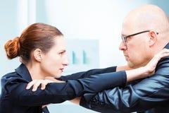 Homme contre le bureau de femme combattant dans le bureau image stock