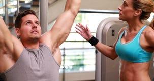Homme convenable à l'aide de la machine de poids pour ses bras tandis que l'entraîneur dirige clips vidéos