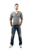 Homme convenable de jeunes dans le T-shirt de v-cou, les jeans déchirés et des espadrilles Photographie stock libre de droits