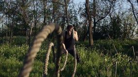Homme convenable de jeunes pratiquant en parc Il emploie des cordes de crossfit pour la formation Temps de jour Sun brille banque de vidéos
