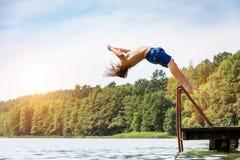 Homme convenable de jeunes sautant dans un lac photos stock