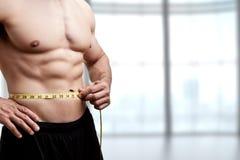 Homme convenable mesurant sa taille Photographie stock libre de droits