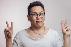 Homme coréen drôle dans les lunettes et T-shirt montrant le signe de paix image stock