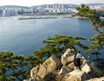 Homme coréen se tenant sur des roches regardant la vue de ville images stock