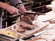 Homme coupant en tranches le pain sur le marché Image libre de droits