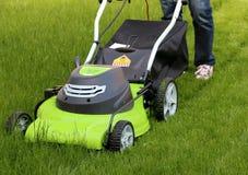 Homme coupant l'herbe avec la tondeuse à gazon photos stock