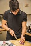 Homme coupant l'oignon rouge avec le couteau pointu dans la cuisine Images stock