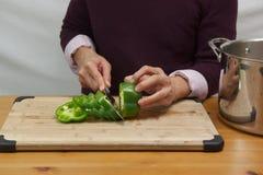 Homme coupant le paprika vert Photographie stock