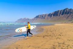 Homme courant avec la planche de surf sur la plage de Famara Images stock