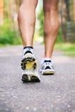 Homme courant Chaussures de course et jambes du coureur masculin dehors sur le RO Image libre de droits