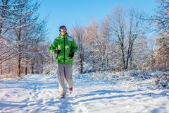 Homme courant d'athlète sprintant dans l'extérieur de formation de forêt d'hiver par temps neigeux froid Mode de vie sain actif photographie stock libre de droits