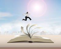 Homme courant et sautant sur le livre ouvert Photos stock