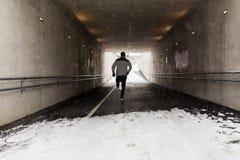 Homme courant le long du tunnel de souterrain en hiver Image libre de droits