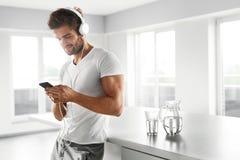 Homme écoutant la musique dans des écouteurs utilisant le téléphone portable à l'intérieur Photos stock