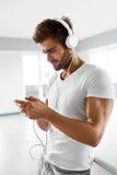 Homme écoutant la musique dans des écouteurs utilisant le téléphone portable à l'intérieur Photo stock