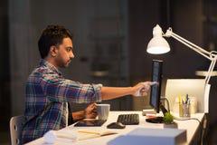 Homme créatif avec l'ordinateur fonctionnant au bureau de nuit Photographie stock libre de droits