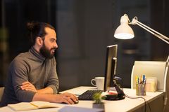 Homme créatif avec l'ordinateur fonctionnant au bureau de nuit Photographie stock