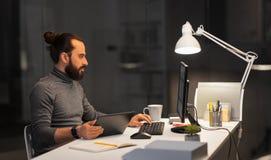 Homme cr?atif avec l'ordinateur fonctionnant au bureau de nuit photographie stock