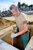 Homme creusant en tombe photo stock