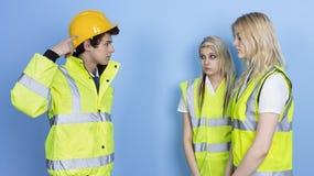 Homme criant au main-d'œuvre féminine pour ne pas utiliser le casque antichoc Photo libre de droits