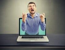 Homme criard émotif sorti de l'ordinateur portable Photos stock
