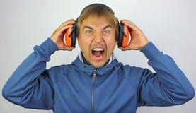 Homme criard avec des écouteurs Image stock