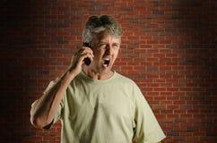 Homme criard fâché sur un téléphone portable Photos libres de droits