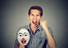 Homme criard fâché tenant le masque de clown exprimant la gaieté photographie stock