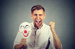 Homme criard fâché tenant le masque de clown exprimant le bonheur de gaieté photographie stock libre de droits