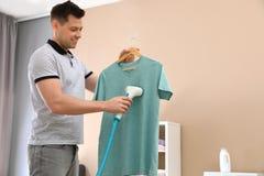 Homme cuisant ses vêtements à la vapeur dans le salon photos libres de droits