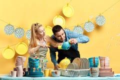 Homme curieux et femme recherchant les sports, la poussière dans le kitchenwear photographie stock