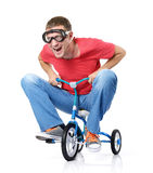 Homme curieux sur une bicyclette d'enfants, sur le blanc Photos stock