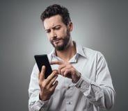 Homme déçu dactylographiant avec son smartphone Photo libre de droits
