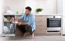 Homme déchargeant le lave-vaisselle photo libre de droits