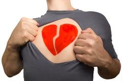 Homme déchirant le T-shirt gris Coeur rouge cassé peint sur le sien Image libre de droits