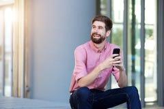 Homme décontracté avec la barbe se reposant dehors avec le téléphone portable Image stock